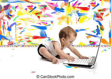 Little baby boy is sitting on floor with his laptop, isolated over white wall, in messy painted room with many colors around