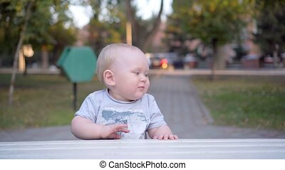 Little baby boy learns to walk along the bench. In the park. Outdoor.