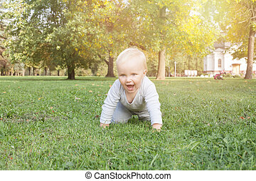Little baby boy lying on the green grass outdoor