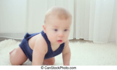 little baby boy of five months, crawling on the floor