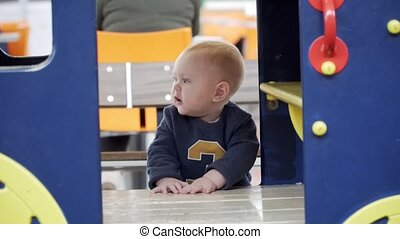Little baby boy playing in a little house on playground.