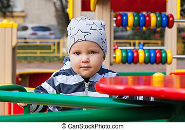 Little baby boy playing on playground outdoors