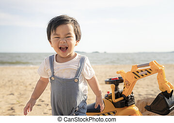 Little baby boy playing on the sand