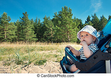 Little baby boy sitting in the stroller on summer day