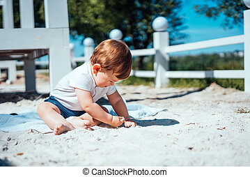 Little baby boy sitting on the sand