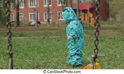Little baby boy walking away in playground