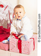 Little baby boy with Decorated Christmas tree indoors