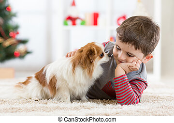 Little baby boy with dog lying on the floor at christmas tree