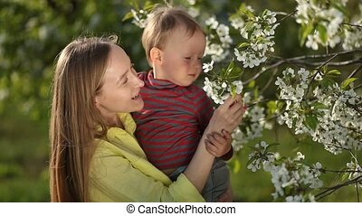 Little baby boy with her mother in blossom garden