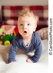 Little baby boy with spiky hair crawling on bed.