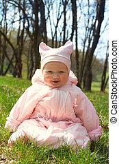 little baby child sitting on a grass