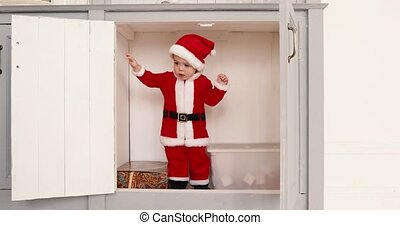 Baby boy in a Santa suit opens closet from inside - Little...