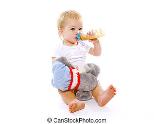 Little baby drinks from a bottle on a white background