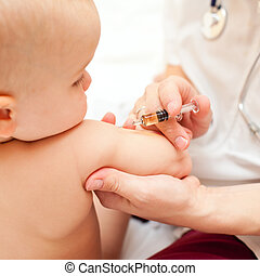 Doctor giving a child an intramuscular injection in arm, shallow DOF