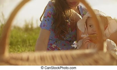 Little baby girl and her mom having picnic on a summer day