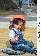 Little baby girl builder with the construction helmet and poster