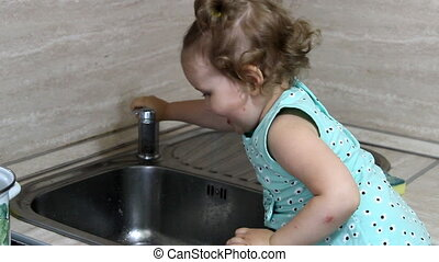 Little baby girl dish washes in the kitchen.