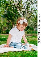 Little baby girl dressed in white polo and jeans, barefoot sitting with tablet on the white fur blanket in park with blossoming trees in the background. Young girl getting into learning on tablet