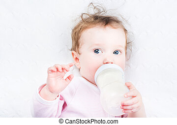 Little baby girl drinking milk out of a bottle