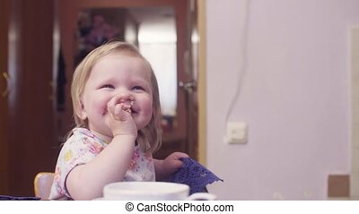 Little baby girl eating cookies and smiling