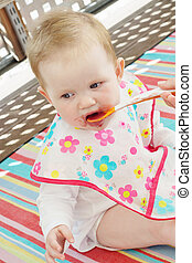 Little baby girl feeding with a spoon in outdoors.