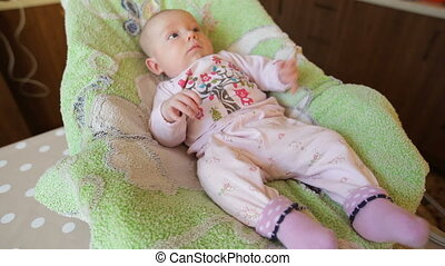 little baby girl in diapers on the green sheet