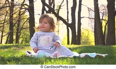 Little baby girl in the park in sunny day