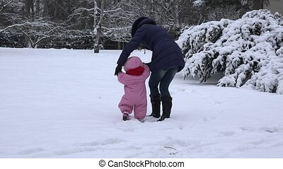Little baby girl learn and her mom learn to walk on snow in winter day. 4K