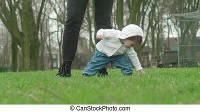 Little baby girl learns to walk with the help of her mother....