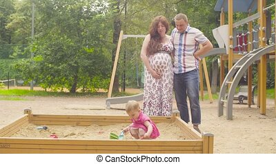 Little baby girl playing in sandbox on playground