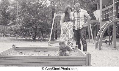 Little baby girl playing in sandbox on playground