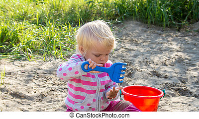 Little baby girl playing in the sand.