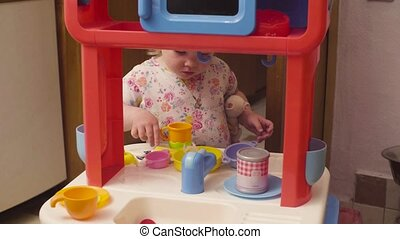 Little baby girl playing in toy kitchen