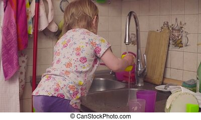 Little baby girl playing near kitchen sink