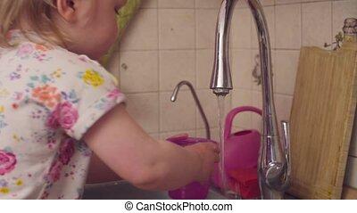Little baby girl playing near kitchen sink