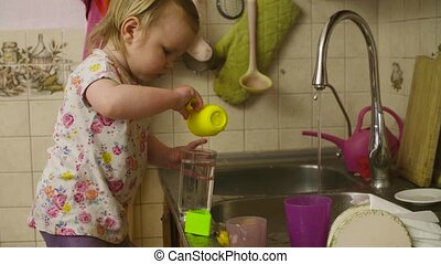 Little baby girl playing washing dishes. She pouring water...