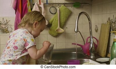 Little baby girl playing washing dishes
