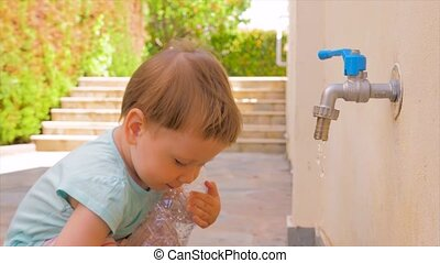 Little baby girl playing with water. Toddler playing with...