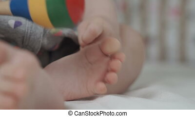 Little baby girl plays with legs