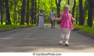 Little baby girl running to her parents