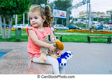Little baby girl sitting on park with toy