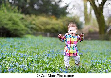 Little baby girl walking in a blue flower field