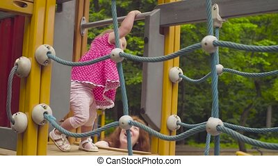 Little baby girl walking on a rope playground