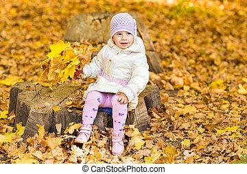 Little baby girl with autumn leaves in the park