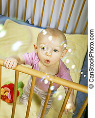 little baby holds on to the baby behind the bed and blows bubbles
