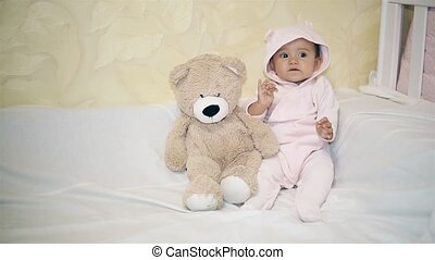 Little baby in a bear costume playing next to a Teddy bear