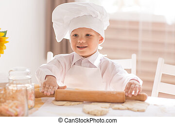 little baby in a cook rolls out the dough with  rolling pin and smiling