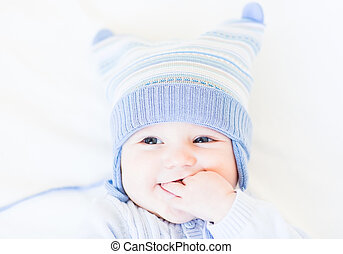Little baby in a funny blue hat on white background