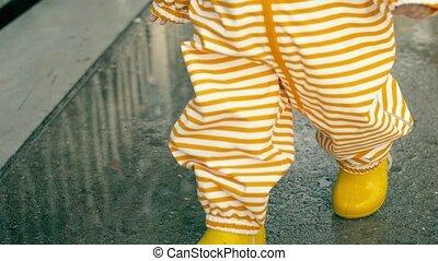 Little baby in orange striped waterproof raincoat and yellow...