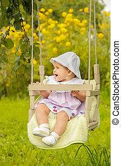 Little baby in Panama swinging on a swing